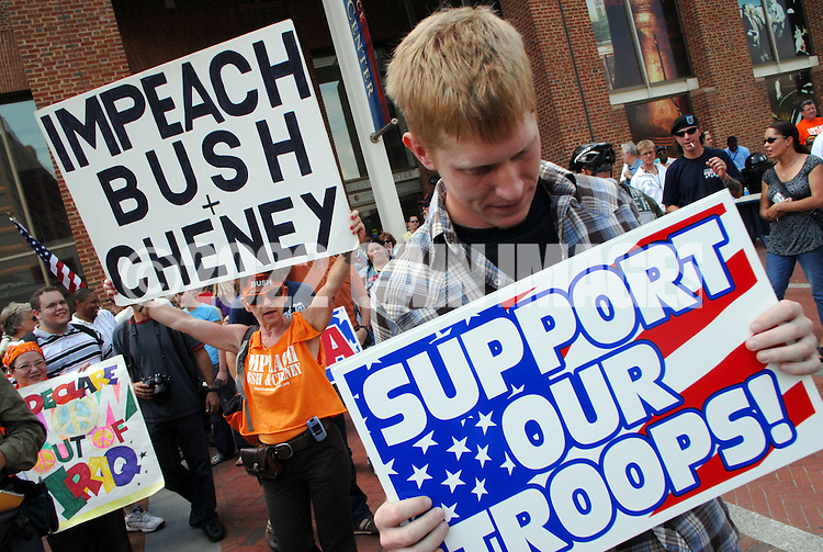 PHILADELPHIA - JULY 24: Monique Frugier of Ardmore (L), Pennsylvania holds an impeach Bush sign during a rally as an unidentified man holds a Support Our Troops sign at the Independence Visitor Center July 24, 2007 in Philadelphia, Pennsylvania. About 100 people attended the rally in which Sheehan was expected to announce her candidacy against Rep. Nancy Pelosi (D-Ca.). (Photo by William Thomas Cain/Getty Images)