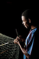 A fisherman untangling his net after a morning catch on the island reserve Nosy Mangabe, Madagascar
