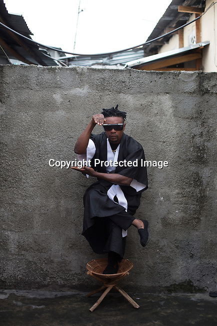 """KINSHASA, DEMOCRATIC REPUBLIC OF CONGO - OCTOBER 10: A Sapeur from the group belonging to The Leopards poses for a portrait February 10, 2015 in Kinshasa, DRC. The word Sapeur comes from SAPE, a French acronym for Société des Ambianceurs et Persons Élégants. or Society of Revellers and Elegant People. and it also means, .to dress with elegance and style"""". Most of the young Sapeurs are unemployed, poor and live in harsh conditions in Kinshasa, a city of about 10 million people. For many of them being a Sapeur means they can escape their daily struggles and dress like fashionable Europeans. Many hustle to build up their expensive collections. Most Sapeurs could never afford to visit Paris, and usually relatives send or bring clothes back to Kinshasa. (Photo by Per-Anders Pettersson)"""