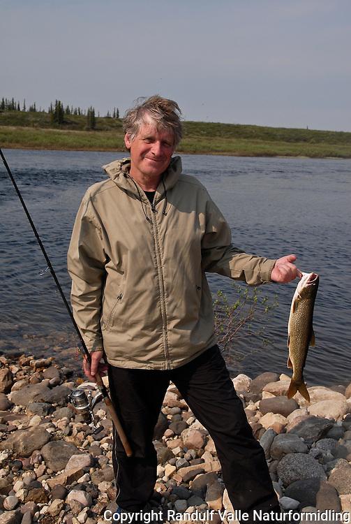 Mann med liten lake trout. ---- Man with small lake trout.