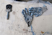 Notting Hill, London, England. Pair of workman's gloves and brush on a plastic sheet.