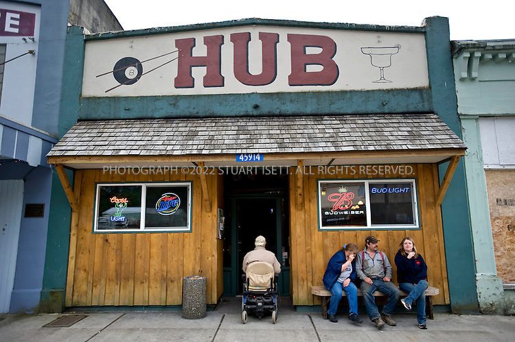6/11/2008--Concrete, WA, USA..Ray Tahanty (center) enters Hub, a bar in Concrete, WA, while xxxx xxxx (2nd from right) enjoys a cigarette outside. The town was named Concrete because of Superior Portland Cement Company's large cement plant in the town. ...Highway 20, cutting through Washington State's Northern Cascades, is one of the last highways built in the state. The final stretch, connecting the west side to the east sides of the mountains wasn't completed until 1972. the road was one of the of the routes promoted by the Federal Writers Projects guides of the 1930s-1940s. ..©2008 Stuart Isett. All rights reserved.