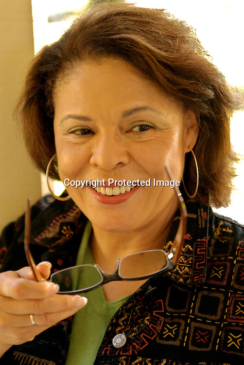 Mature woman holding glasses, smiling