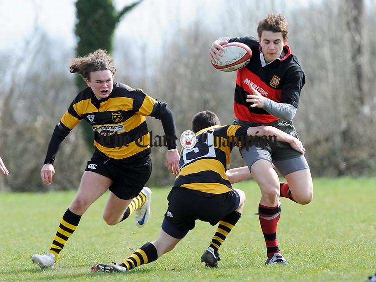 Steven Collins of Enis is tackled by Young Munsters' Andrew Casey during their U-18 League game at Lees Road. Photograph by John Kelly.