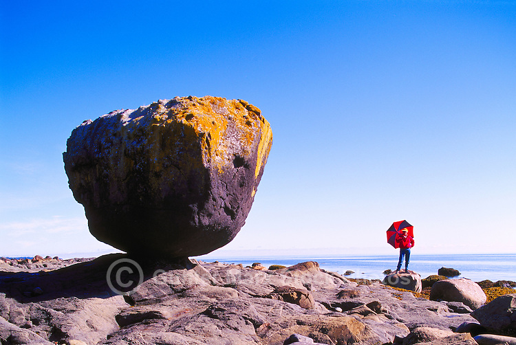"Haida Gwaii (Queen Charlotte Islands), Northern BC, British Columbia, Canada - Woman standing beside ""Balance Rock"" at Low Tide, near Skidegate on Graham Island (Model Released)"