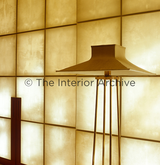 Detail of the lampshade of a floor lamp infront of a calf-skin parchment sliding screen