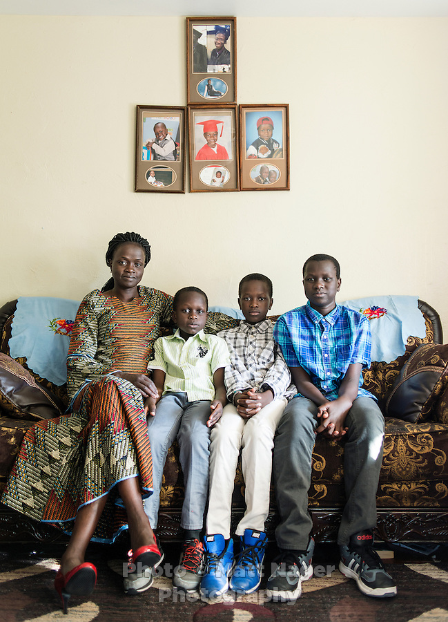 Mary Kuanen at home with her children Bang Malual (age 13 in blue), Emmanuel Malual (age 7 in green), and Malual Malual (age 10 in white)in Denver, Colorado, Friday, October 21, 2016. Williams a refugee from Sudan moved to Denver 11 years ago with her husband and children. Five years ago her husband was murdered in a mistaken identity gang shooting. <br /> <br /> Photo by Matt Nager