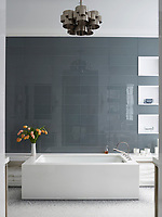 The stylish grey and white bathroom has a simple free-standing bathtub and tiled walls.