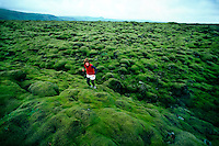 A traveler hikes across an expanse of spongy moss in southeast Iceland.