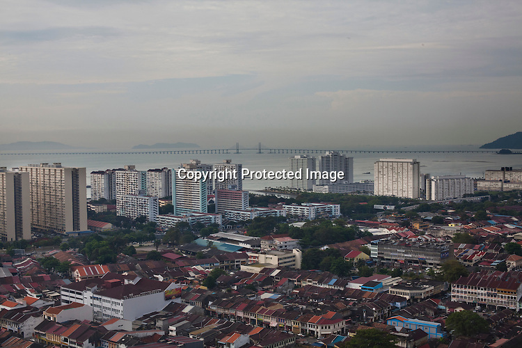 The famous Penang bridge is seen in the distance against the overview of capital Georgetown of Penang, Malaysia. Photo: Sanjit Das/Panos