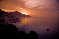 The sky turns orange as the sun sets over the Amalfi Coast of Italy