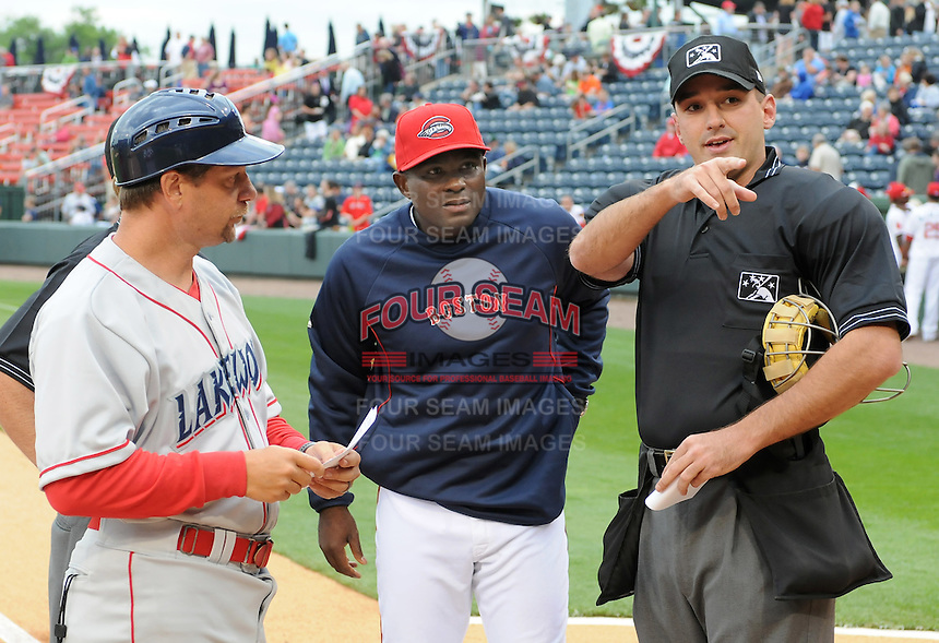 New manager Carlos Febles (33) of the Greenville Drive, center, meets with Lakewood BlueClaws manager Mickey Morandini (12), left, and home plate umpire Brian Miller before the Opening Day game, April 5, 2012, at Fluor Field at the West End in Greenville, South Carolina. (Tom Priddy/Four Seam Images)