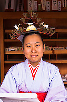 A girl working at Osaka`s Tsumiyoshitaisha shrine wearing a very distinctive hat.