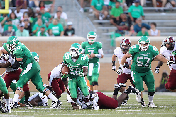 Denton, TX - SEPTEMBER 22: Running back Antoinne Jimmerson #22 of the North Texas Mean Green gets blocks from offensive linesman Coleman Feeley #70 and breaks a tackle against linebacker Jacoby Thomas #56 of the Troy Trojans at University of North Texas Apogee Stadium in Denton on September 22, 2012 in Denton, Texas. (Photo by Rick Yeatts)