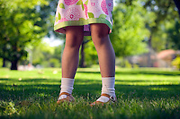 Legs of little girl in flower dress showing her knees in the her yard