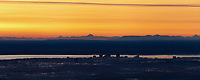 Sunset over the city of Anchorage situated along Cook Inlet with the Alaska Range mountains in the background.