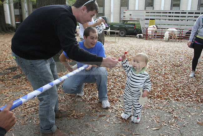 Kitty Karnival is part of the Homecoming celebration at UK.  Student organizations set up tables for children to play games and receive candy on Tuesday, October 19, 2010.  Powers Yurk, 18 months, gets candy from Jordan Young and James Tewes, members of STAT.  Photo by Latara Appleby | staff