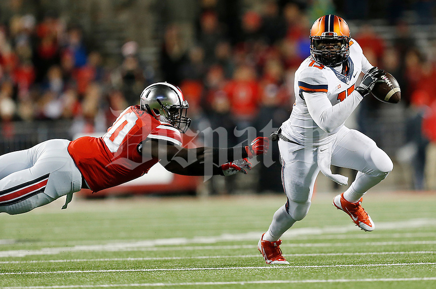 Illinois Fighting Illini quarterback Aaron Bailey (15) evades a tackle from Ohio State Buckeyes defensive lineman Jalyn Holmes (10) in the third quarter the college football game between the Ohio State Buckeyes and the Illinois Fighting Illini at Ohio Stadium in Columbus, Saturday night, November 1, 2014. The Ohio State Buckeyes defeated the Illinois Fighting Illini 55 - 14. (The Columbus Dispatch / Eamon Queeney)