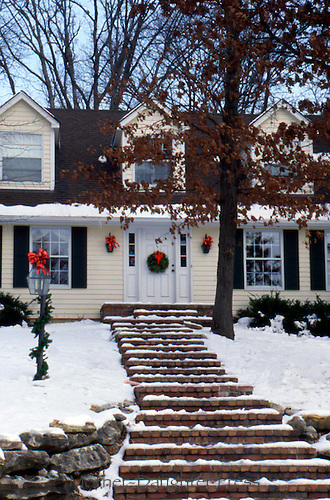 Cape cod style house with yellow clapboard decorated for Christams with bows on gas lamps and boughs on lamsp and wreath on door on snowy December day, Missouri, USA