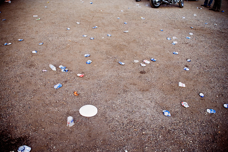 Empty beer cans litter the parking lot at the Testicle Festival at the Rock Creek Lodge in Clinton, MT.  The Rock Creek Lodge in Clinton, MT, has hosted the annual Testicle Festival since the early 1980s.  The four day festival and party revolves around the consumption of so-called Rocky Mountain Oysters, which are deep-fried bull testicles.