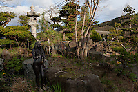 Lanterns, and a statue in the abandoned village of Tsushima in Fukushima, Japan. Friday May 4th 2012. After the explosions at the Daichi nuclear plant caused by the March 11th 2011 earthquake and tsunami. High levels of radioactive contamination in this village have made it uninhabitable.