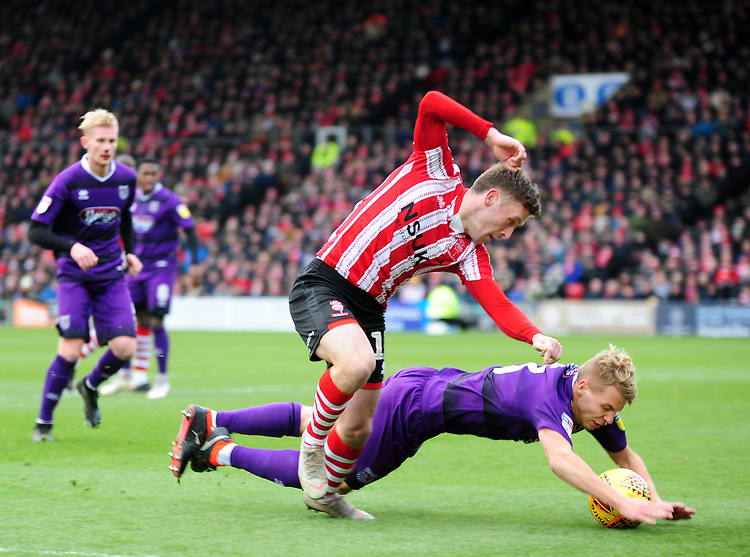 Grimsby Town's Sebastian Ring is fouled by Lincoln City's Shay McCartan<br /> <br /> Photographer Andrew Vaughan/CameraSport<br /> <br /> The EFL Sky Bet League Two - Lincoln City v Grimsby Town - Saturday 19 January 2019 - Sincil Bank - Lincoln<br /> <br /> World Copyright &copy; 2019 CameraSport. All rights reserved. 43 Linden Ave. Countesthorpe. Leicester. England. LE8 5PG - Tel: +44 (0) 116 277 4147 - admin@camerasport.com - www.camerasport.com