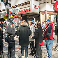 An NYPD officer assists visitors on opening day of Super Bowl Boulevard in Midtown Manhattan in New York on Wednesday, January 29, 2014. Despite the game being held in New Jersey on February 2 sports fans are expected to pack New York to take part in the multitude of activities planned around the game including the 13 block stretch of Broadway, running from 34th street through 47th street that will host Super Bowl Blvd. from January 29 to February 1. (© Richard B. Levine)