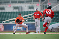 Baltimore Orioles first baseman Ian Evans (63) waits to receive a throw as Gilberto Jimenez (64) runs to first base during a Florida Instructional League game against the Boston Red Sox on September 21, 2018 at JetBlue Park in Fort Myers, Florida.  (Mike Janes/Four Seam Images)