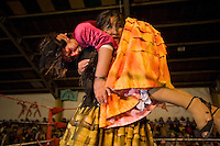 Wrestler Yenifer Dos Caras (fighting name), Anna Luisa Yujra (real name) carries 17 year old Alicia Flores (fighting name), Patricia Kaly (real name) during a fight at the Multifuncional building in El Alto. Patricia and Anna are Cholitas, wrestlers of native Aymara descent. When Cholitas fight they wear traditional costume. The blood on Patricia's face is believed to be fake, but the wrestlers insist that it is real..