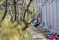 Pictured: A migrant sneaks in through the fence to get belongings at Moria camp on Lesbos island.<br /> Re: Up to 4,000 migrants were evacuated from the Moria camp on the Greek island of Lesbos after a large fire destroyed tents and prefabricated homes.<br /> No injuries have been reported, and some migrants have now been allowed to return to the camp.<br /> Police are investigating whether the fire was deliberate, but an aid worker said it started after a food dispute.<br /> There are some 5,600 refugees currently in Lesbos, according to the UN, but the island only has capacity for 3,600.<br /> The fire destroyed 30% of the camp, according to Aris Vlashopoulos, an aid worker with the Swiss charity SAO.<br /> &quot;People are returning to the camp now as I can see. But the biggest number of the refugees are already on the streets, sleeping outside,&quot; he added.