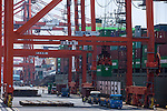 Tokyo, Japan - Workers manage containers from ship docked in cargo area at a port in Tokyo, May 22, 2013. Japan posts a record-high of 879.9 billion yen ($8.6 billion USD) trade deficit for April as the weaker yen caused the increase the costs of imports.