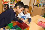 Education Preschool 4 year olds two boys playing together constructing building with magnetic blocks