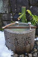 Kyoto City, Japan<br /> Kiyomizu Temple, bamboo ladles resting on hishaku (rack) over a chuzua (ritual washing  water trough)