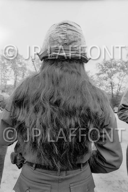 Fort Dix, NJ - May, 1980 <br /> A female soldier&rsquo;s red locks flow down her back from under a green camouflage army helmet. <br /> Fort Dix, New Jersey, mai 1980.<br /> Deux jeunes viennent d&rsquo;&ecirc;tre incorpor&eacute;s dans l&rsquo;arm&eacute;e. Les femmes pourront d&eacute;sormais faire partie des unit&eacute;s de combat.