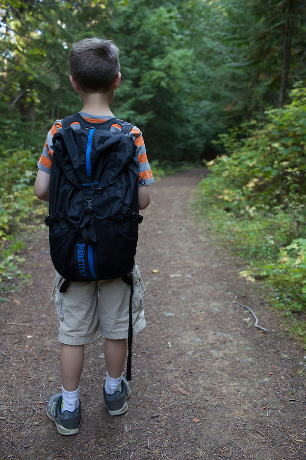 An 8 year old boy hikes along a well-established trail in Bonner County, Idaho in a pair of shorts.
