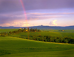 Tuscany, Italy        <br /> A clearing storm at sunset creates a rainbow over the rolling hills and farmlands near Pienza in the Val d'Orcia