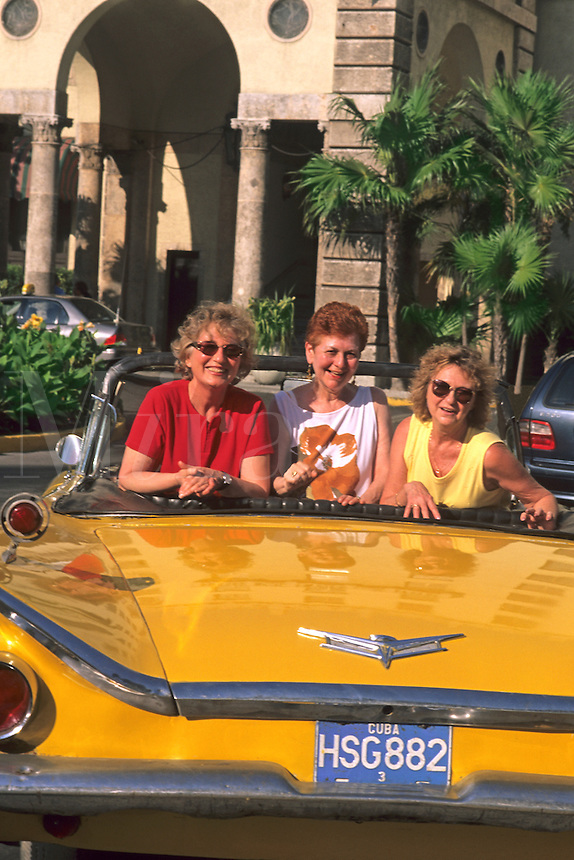 Smiling tourists in a 1950's convertible taxi.  Havana, Habana, Cuba.