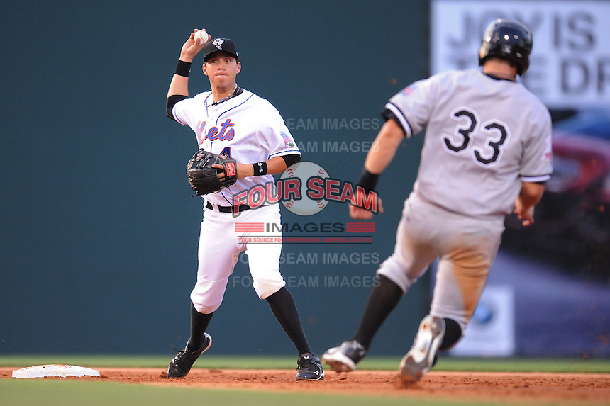 Savannah Sand Gnats Wilmer Flores turns two over a hard sliding Ian Gac of the Hickory Cawdads during the South Atlantic League All Star Game at Fluor Field in Greenville, South Carolina June 22, 2010.   The game ended in a 5-5 tie.  Photo By Tony Farlow/Four Seam Images