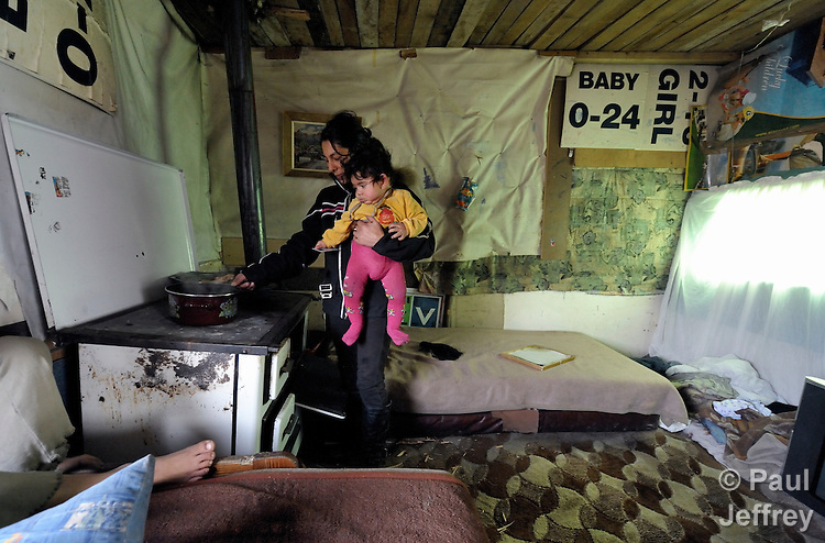 Ivana Ibraimovic holds her 8-month old son Rasim as she cooks inside their house in a Roma settlement in Belgrade, Serbia. The families that live here, many of whom survive from recycling cardboard and other materials, are under constant threat of eviction in order to make way for new high-rise office buildings. Ibraimovic heats her house by opening the oven door on the wood-fired stove behind her. Note: residents of this settlement were forcibly evicted in April 2012, two months after this photo. Many were relocated in metal shipping containers at the edge of the city.