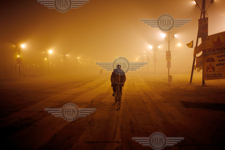 A cyclist rides through the almost empty grounds set up for the Ardh Kumbh Mela.