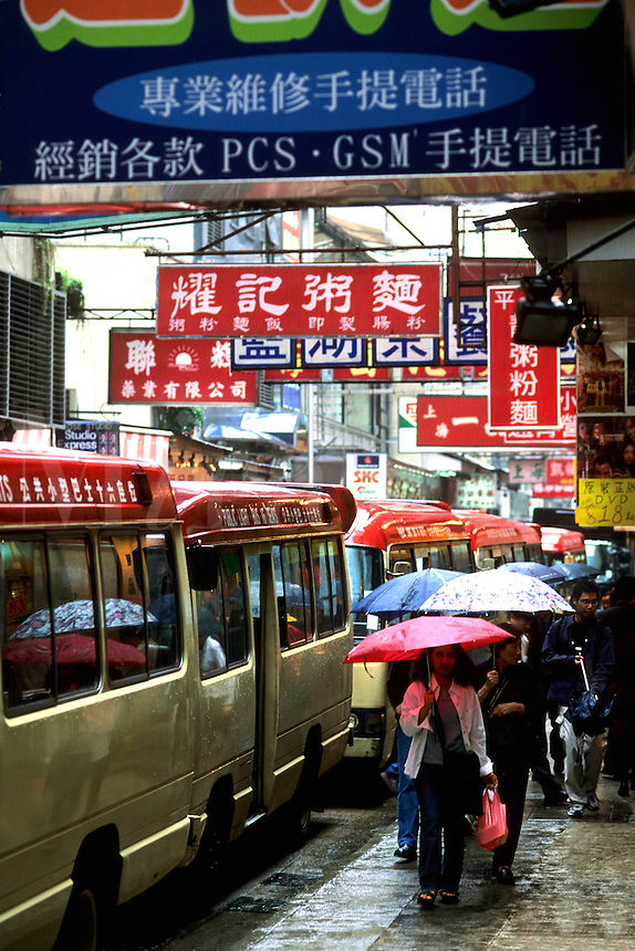 All the glitter and color of Hong Kong today in the Central District with umbrealls buses traffic and walkers to wor