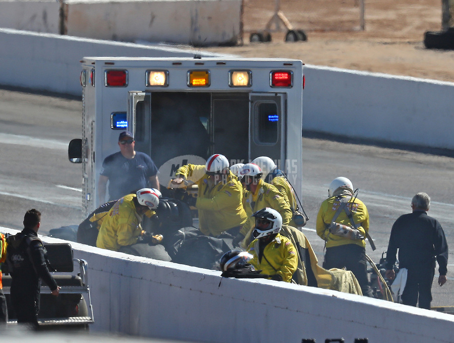 Feb 25, 2018; Chandler, AZ, USA; Members of the NHRA Safety Safari rescue crews tend to funny car driver John Force after crashing during the Arizona Nationals at Wild Horse Pass Motorsports Park. Mandatory Credit: Mark J. Rebilas-USA TODAY Sports