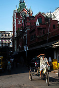 A day wage labourer rides past the century-old Sir Stuart Hogg Market, also known as the New Market in Kolkata, West Bengal  on Friday, May 26, 2017. Photographer: Sanjit Das