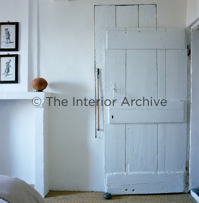 The open bedroom door is an antique wooden one painted white like the walls