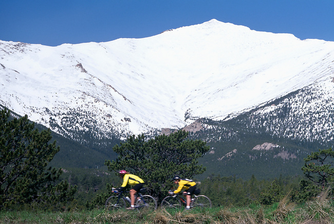 A couple cycling during the Courage Classic bike race beneath Mt Meeker, Rocky Mtns, CO