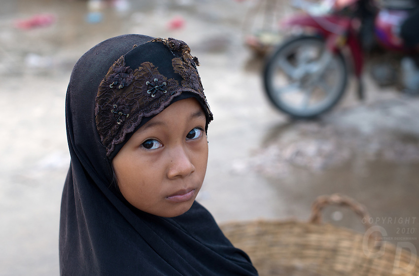 A young muslim girl at the early  morning Whole sale fish market on the Banks of the Mekong River, outskirts of Phnom Penh, Cambodia