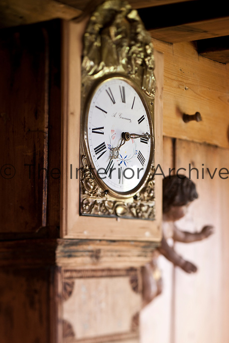 Detail of the ornate face of the grandfather clock in the dining room