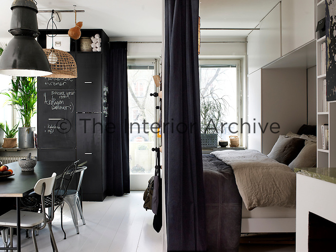 Thick velvet curtains (when drawn) enclose the bedroom alcove and shield it from the kitchen/dining area. The bed is made with natural materials such as linen, cotton and suede