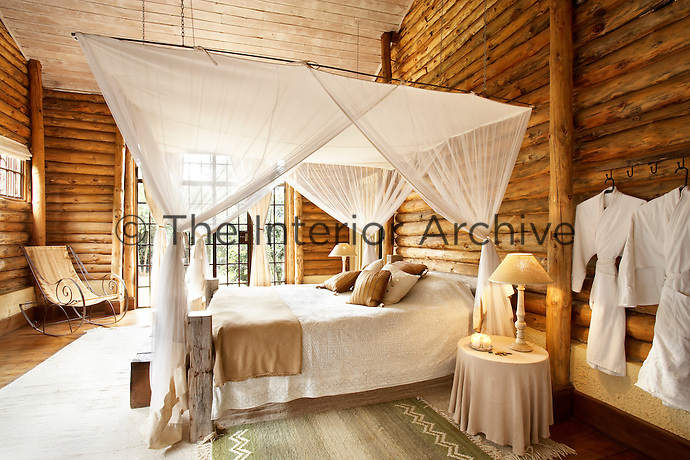 A bedroom in a luxury guest house has a rustic feel. The talents of regional artists provide many of the finishing touches.  Recycled wood, from a dhow, was used for the canopy bed and the metal rocking chair was welded by a local artisan.