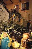 "Switzerland. Canton Tessin. Vira Gambarogno. The old town shows an exhibit of various Nativity scenes, illuminated at night for the Christmas holiday season. A Nativity Scene, may be used to describe any depiction of the Nativity of Jesus in art, but in the sense covered here, also called a crib or in North America and France a crèche (meaning ""crib"" or ""manger"" in French). It means a three-dimensional folk art depiction of the birth or birthplace of Jesus, either sculpted or using two-dimensional (cut-out) figures arranged in a three-dimensional setting. Christian nativity scenes, in two dimensions (drawings, paintings, icons, etc.) or three (sculpture or other three-dimensional crafts), usually show Jesus in a manger, Joseph and Mary in a barn (or cave) intended to accommodate farm animals. The Star of Bethlehem.  Passer-by and fir. © 2007 Didier Ruef"